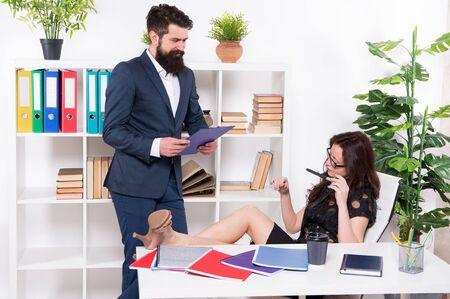 jefe y empleado. dominación femenina. hombre contra mujer. pareja de negocios en la oficina de trabajo. Confianza empresaria relajarse mientras el asistente de hombre trabaja. El empresario da instrucciones a la secretaria perezosa. Foto de archivo
