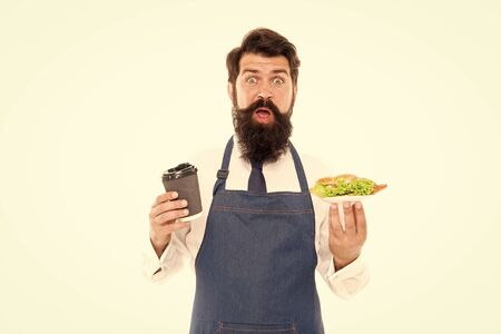 Cafe food concept. Enjoy your meal. Guy serving croissant stuffed lettuce and fresh vegetables. Healthy food. Delicious croissant. Man bearded waiter wear apron carry plate with food and coffee cup