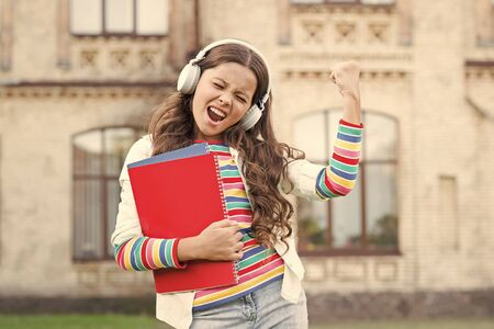 Digital technologies for learning. Schoolgirl hold workbooks and headphones. Technologies for studying. Audio course. Modern technologies. Elearning and modern methods. Listening school book Banque d'images