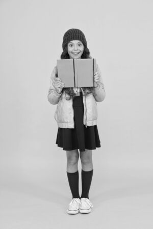 School girl. Happy girl back to school in autumn. Little girl borrow books in library. Small girl smile in formal school uniform. Education and learning. Knowledge and information