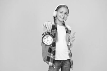 Beginning of lessons. Time go school. School time. Happy girl hold alarm clock counting minutes. Knowledge day. Classes schedule. Schoolgirl hold alarm clock yellow background. School timing concept