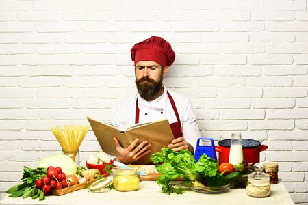 Cook with serious face in uniform sits by vegetables Banque d'images