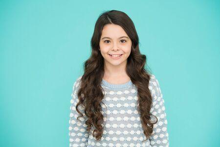 Fondo azul niña. Niña sonriente con pelo largo. Belleza y salud. Infancia y niñez. Día Internacional de la Infancia. Cuidado de los niños. Infancia feliz. Niño hermoso. Chica emocional