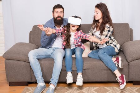 Lot of concern surrounding children using VR headsets. Daughter stuck in virtual reality. Digital world. Virtual life and dependence. Parents worry about kid in virtual reality. Virtual cyber gaming Stock Photo