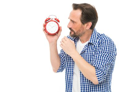 Time is marching on. Senior man looking at clock. Bearded man with mechanical clock in hand. Mature timekeeper with analog clock. Mature man holding alarm clock. Scheduling time Stock Photo