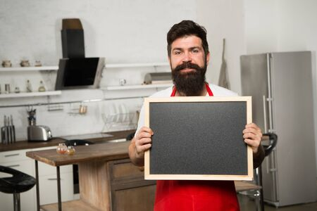 Chef at work. I need you at the kitchen. Hipster in kitchen. Mature male. Bearded man cook. Bearded man in red apron. Man chef with board, copy space. Restaurant or cafe menu. Advertisement