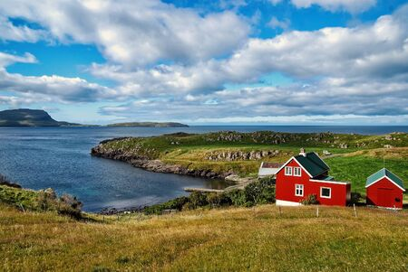 Houses on sea coast on cloudy sky in Torshavn, Denmark. Wooden houses on seascape. Beautiful landscape view. Summer vacation in country. Architecture and design. Ecology and environment.