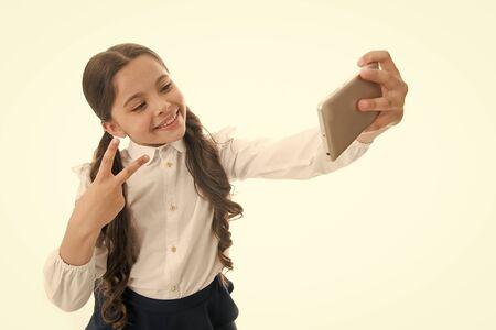 Girl cute long curly hair holds smartphone taking selfie white
