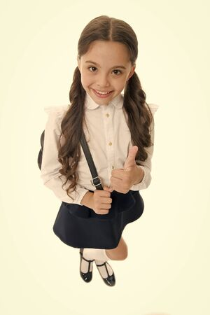 Schoolgirl shows thumb up gesture, isolated white