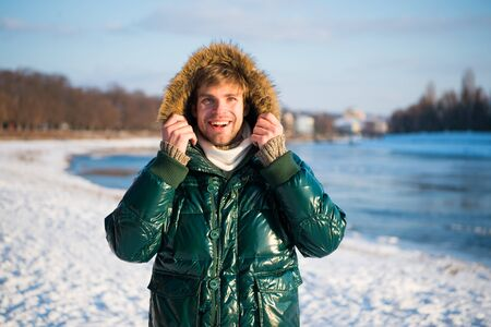 Travel and vacation concept. Man warm jacket snowy nature background. Wind resistant clothes. Winter favorable weather conditions. Sunny winter day. Winter menswear. Winter outfit. Guy jacket hood