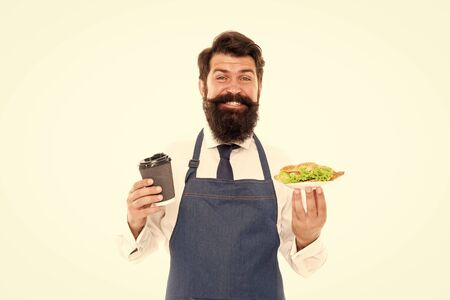 Cafe food concept. Man bearded waiter wear apron carry plate with food and coffee cup. Enjoy your meal. Guy serving croissant stuffed lettuce and fresh vegetables. Healthy food. Delicious croissant