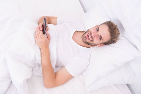 phone addiction tips. he is blogging. flirting and sending text message. internet addiction and mobile abuse. man in bed chatting. man use smartphone from the early morning. whole world in phone