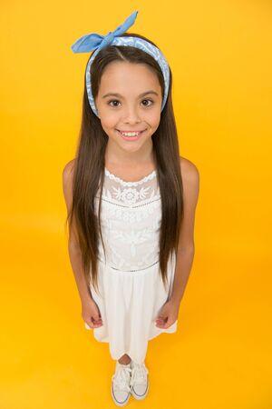 Chemische Haarglättung. Entzückendes kleines Mädchen mit perfekten langen Haaren. Shampoo und Spülung. Friseursalon. Professionelle Tipps zur Haarpflege. Internationaler Kindertag. Süße Babykopftuchschleife