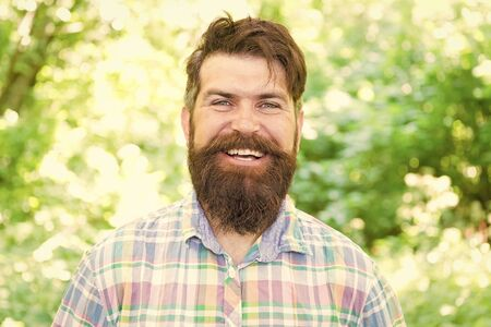 Making happiness possible. Happy hipster with smiling face on summer landscape. Bearded man with long beard and big smile shining with happiness on sunny day. Happiness is a choice. Happiness concept