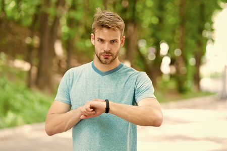 Sportsman training with smart watch. Set up fitness tracker. Fitness coach. Useful settings. Wrist band gadget. Athlete check fitness tracker nature background. Athlete look pedometer gadget
