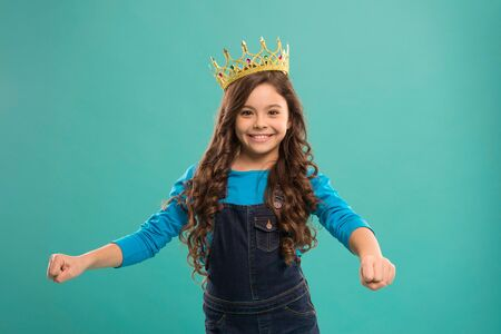 Curly hairstyle. Gorgeous hair award. Kid wear golden crown symbol of princess. Girl cute baby wear crown blue background. Princess concept. Every girl dreaming to be princess. Little princess