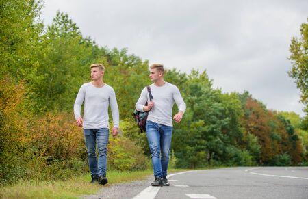Problemas de transporte. Mochila de hombre caminando por la carretera. Los gemelos caminan por la carretera. Fondo de naturaleza de amigos de hermanos. Largo camino. Concepto de aventura. Chicos haciendo autostop en la carretera. Parada de auto de viaje de viajero turístico Foto de archivo