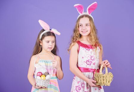 Some bunny loves you. Small girls in bunny headband for Easter celebration. Little girls wearing Easter bunny ears. Cute Easter bunnies bringing eggs. Easter egg is symbol of new life 写真素材