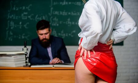 Sexy seduction. Sexy butt red latex skirt in front of teacher. Looking for help with homework. Seductive offer. Sexual bribe. Check knowledge. Buttocks fetish. Sexy student. University high school 版權商用圖片
