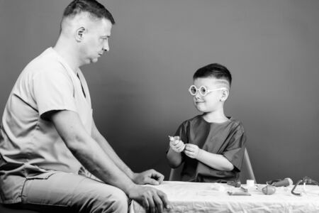 Medical examination. Boy cute child and his father doctor. Hospital worker. Medicine concept. Kid little doctor sit table medical tools. Illness treatment. Dad and son medical dynasty. Health care Stock fotó