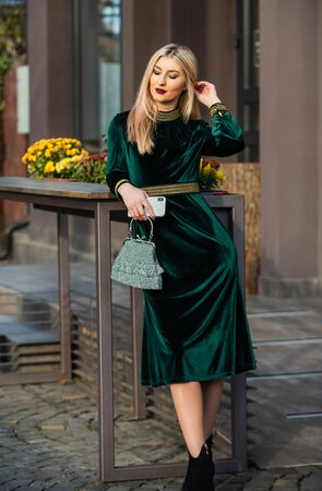 Glamorous clutch accessory. Fashion blog. Elegant woman in green velour dress. Velvet fashion trend. Silk velvet. Glamour velvet textile. Sexy woman outdoors. modern life. Girl carry handbag