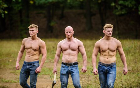 Determined to win. three muscular men with axe. athletic man use ax. brutal and strong male. sexy guys six packs and biceps. protein or steroids. bodybuilding concept. relax after work in the forest Banque d'images