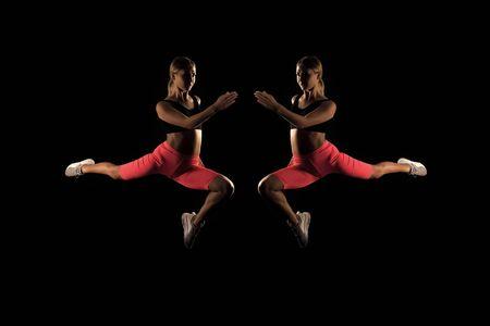 움직임이 얼어붙었습니다. 반사 여자 운동 선수는 점프 비행을 실행합니다. 더 빨리 달리는 방법. 스피드 트레이닝 가이드. 실행 속도를 향상시킵니다. 검은 배경에 소녀 주자입니다. 스포츠 라이프 스타일과 건강 개념입니다. 실행 시작