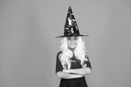 Looks perfect. trick or treat. supernatural charmer gray hair. kid enchantress orange background. happy halloween. magic fantasy. smiling girl halloween party. mystery witch. small child witch hat Stock Photo