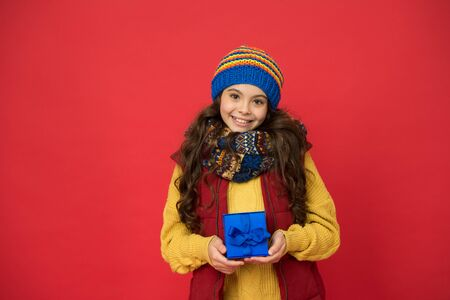 Holidays season. Happy childhood. Christmas gifts and souvenirs. Winter holidays. Happy kid in winter outfit red background. Pick some winter gifts for yourself. Wish list. Consume consciously Stockfoto