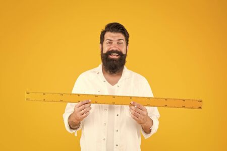 There is no substitute for a great teacher. Happy teacher holding ruler on yellow background. Maths teacher smiling with mathematical instrument ready for lesson. School teacher welcoming students