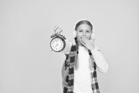Classes schedule. Schoolgirl hold alarm clock yellow background. School timing concept. Beginning of lessons. Time go school. School time. Happy girl hold alarm clock counting minutes. Knowledge day Banque d'images