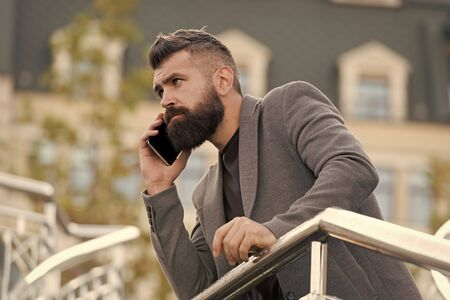 Mobile is lifestyle. Project manager use mobile device outdoor. Bearded man talk on mobile phone. Mobile business communication. Modern life. New technology Reklamní fotografie