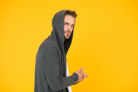 I will be back. Comfy garment for daily life. Fashion man yellow background. Fashion look. Handsome guy wear fashionable mantle with hood. Casual menswear. Fashion trends. Modern clothes for youth