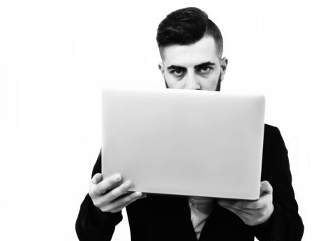 Successful businessman with serious look holds white laptop