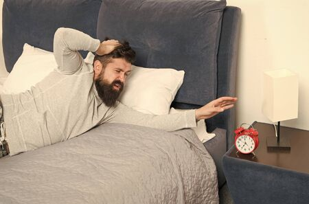hate noise of alarm clock. having terrible headache. Man at home. Health care concept. need more relax in bed. stressed and unhappy man. bearded man hipster want to sleep. early morning awakening