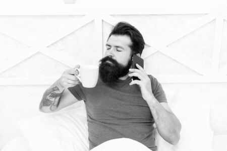 Pleasant conversation. Good morning. Hello dear. Bearded man using mobile technology in bed. Handsome guy talking on phone and drinking coffee at home. Modern life new technology. Technology concept 版權商用圖片