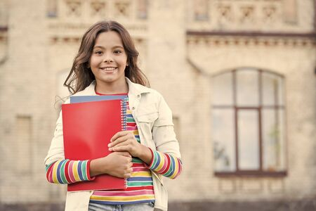 Taking extra course for deeper learning. School education. Choice course. Modern education. Kid smiling girl school student hold workbooks textbooks for studying. Education for gifted children