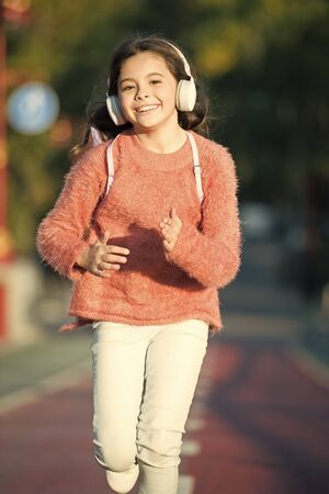Music for autumn cozy mood. Listening songs. Melody for good mood. Drive by song. Enjoy music outdoors fall warm day. Audio file. Kid girl running jogging with modern wireless headphones