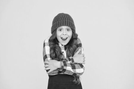 She is cold. Unhappy little child feel cold yellow background. Small girl shiver in cold weather headwear. Crispy autumn or winter season. Chilly and cold. Coldness