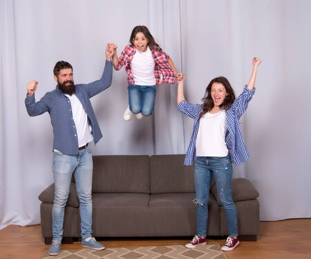 Higher. Friendly family jump couch Mom dad and daughter relaxing. We are family. Happy family spend weekend together. Our home made for fun. Togetherness and bonds. Good vibes. Positive emotions 版權商用圖片