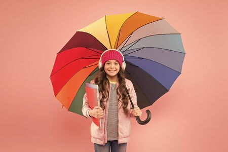 Designed for rainy weather. Little school girl hold colorful umbrella on pink background. Small child back to school in autumn. Adorable kid in earphones go to school on rainy day. The best school