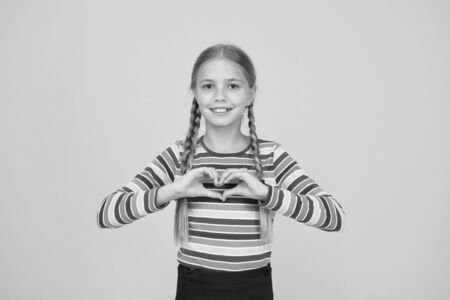 Share love. Adorable girl beautiful face. Little girl. Small child with cute braids hairstyle on yellow background. Child care concept. Preteen girl colorful clothes. Childrens shop store mall