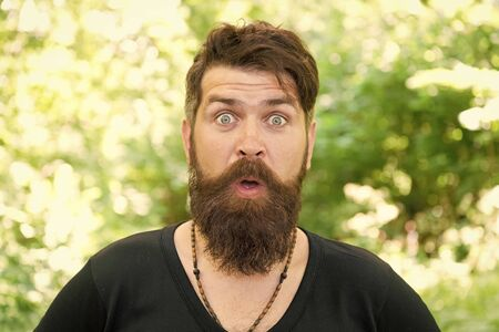 Feeling good fabulous mustache. Bearded man with stylish mustache shape. Brutal hipster with textured mustache hair on unshaven face. Surprised guy wearing long beard and mustache on natural outdoor