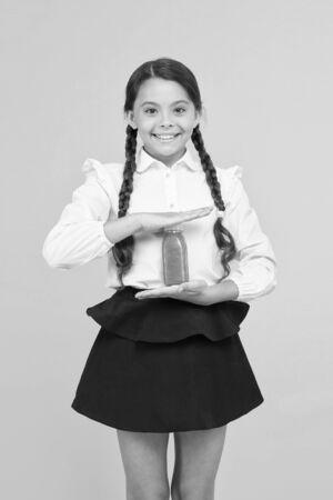 Keeping you energetic. Happy energetic schoolchild holding juice bottle on yellow background. Little girl with long hair braids feeling healthy with energetic drink. Smart and energetic 版權商用圖片
