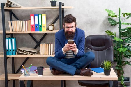 Application smartphone. Take break to check social networks. Online relax. Self care. Relaxation techniques. Mental wellbeing and relax. Man bearded manager formal suit sit lotus pose relaxing