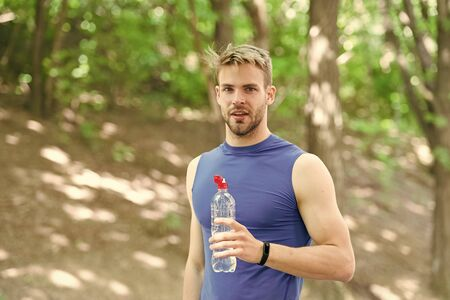 Man athlete sport clothes care about water balance. Healthy lifestyle. Athlete drink water after training in park. Vitamins and minerals. Refreshing drink. Man athletic sportsman hold bottle water 版權商用圖片