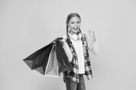 Shopping and sale on black friday. Addicted consumer. Dive into shopping. Happy child with paper bags. Little girl smile with shopping bags on yellow background. Holiday preparation and celebration