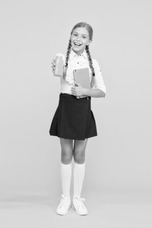 This is my favorite taste. Healthy nutrition. Schoolgirl holding juice bottle on yellow background. Quenching thirst during school time. Healthy snack fruit smoothie. Smoothie detox. Yummy smoothie