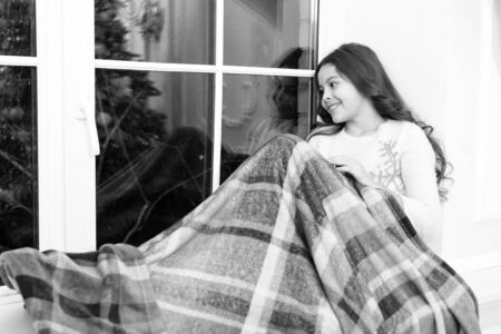 New year. Little girl child looking at window. Present xmas. Winter memories. Kid at home relaxing on cozy window sill. Winter feast. Waiting for Santa. Happy winter holidays. Small girl at home