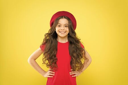 Following her personal style. little girl in french style hat. happy girl with long curly hair in beret. parisian child on yellow background. summer fashion and beauty. childhood. hairdresser salon